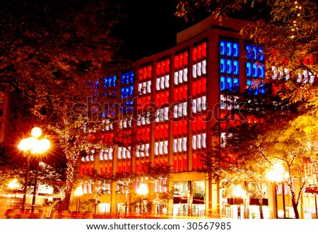 office building with the american flag lighting in the evening