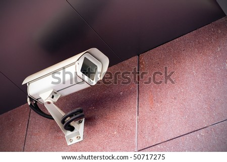 Office building with white security camera under a ceiling