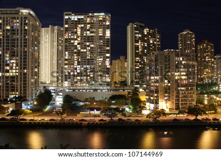 Office buildings and apartments form a partial skyline of Honolulu along the Ala Wai Canal near the Hawaii Convention Center at night