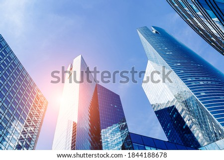 Office buildings in financial district with sun light and sky reflecting in the modern glass walls of skyscrapers. Business background. Low angle of view Photo stock ©