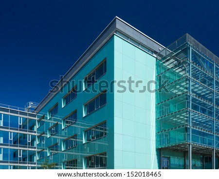 Office buildings with glass reflecting surroundings and clear blue sky