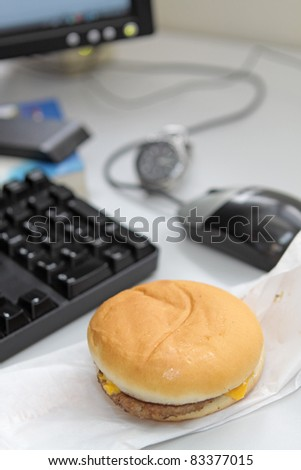 Office business lunch food cheese hamburger, desktop and financial newspaper on office desk