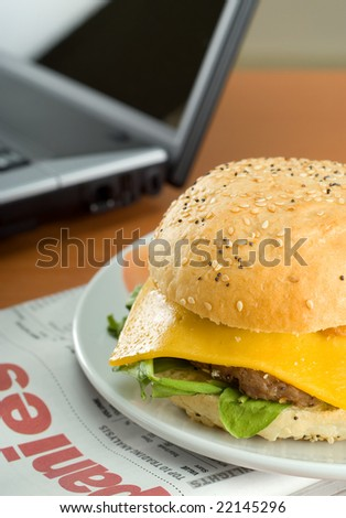 Office business lunch food cheese hamburger, laptop and financial newspaper on office desk