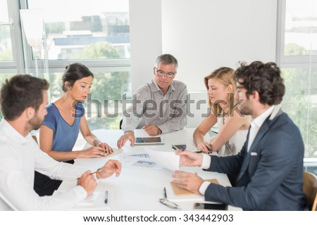 Office business meeting. The team is sitting at a table in a luminous white open space, brainstorming some new ideas. The men are wearing suits and shirts. The boss is exposing a new blueprint #343442903