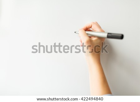 office, business, people and education concept - close up of hand with marker writing or drawing something on white board or wall