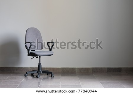 Office chair against a gray wall with sunlight.