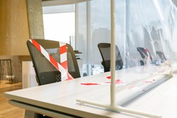 Office chairs marked with white and red tape looking through the plastic physical wall. New normal Concept for social distancing in offices during the Covid-19 pandemic. Precaution and safe workspace.