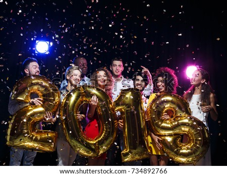 Office christmas party. Group of joyful colleagues having fun at new year celebration. Happy smiling people holding golden number balloons, 2018 year symbol. Greeting card for co-workers mockup #734892766