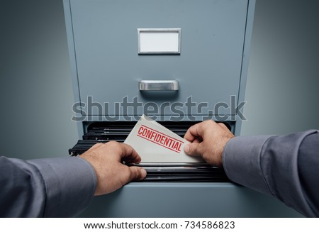 Office clerk searching for files in the filing cabinet, he finds a folder with confidential information inside, personal point of view