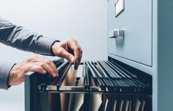 Office clerk searching for files into a filing cabinet drawer close up, business administration and data storage concept
