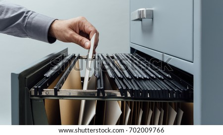 Office clerk searching for files into a filing cabinet drawer close up, business administration and data storage concept #702009766