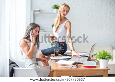 Office coffee break. Businesswoman showing something to colleague on laptop.