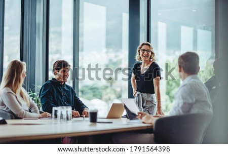 Office colleagues having casual discussion during meeting in conference room. Group of men and women sitting in conference room and smiling.