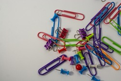 Office.Colored paper clips lie together.Around white background. Blue, yellow, purple, green, pink and orange. Plastic paper clips for documents. Office and educational equipment. Tools for paper work