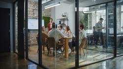 Office Conference Room Meeting: Female Chief Executive Talking to a Diverse Team of Professional Businesspeople. Creative People Listen to CEO Discuss Design, Data Analysis, Plan Marketing Strategy