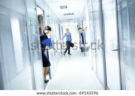 Office corridor and people looking out from the rooms