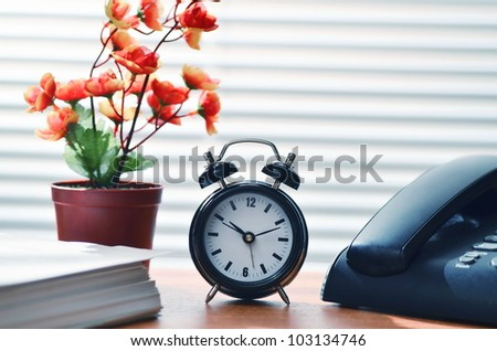 Office desk arrangement showing clock, phone, flower decoration and paperwork. Can be use to show work efficiency concept.