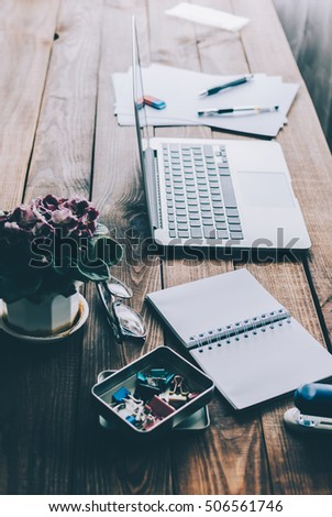 Office desk background: laptop, notebook, flower, and other on rustic brown wooden table #506561746