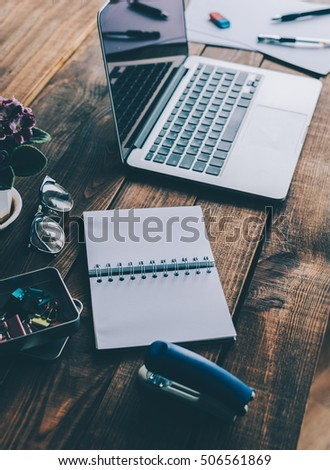 Office desk background: laptop, notebook, flower, and other on rustic brown wooden table #506561869