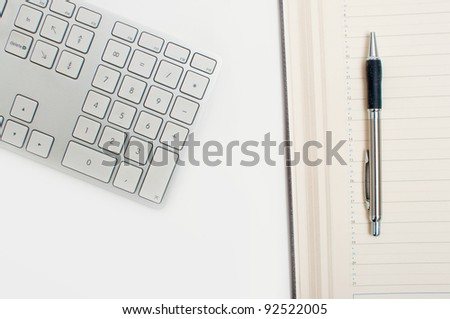 Office desk. Computer keyboard, agenda and a pen on table top.