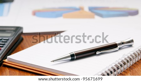 Office desk concept with pad, pen, calculator in view