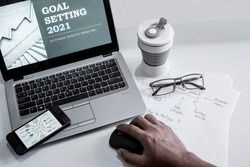 Office desk for Goal Setting 2021 presentation set up with notebook, smartphone, reading glasses, paper note and tumblr