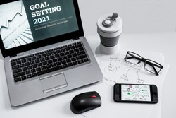 Office desk items with laptop for presentation of Goal setting 2021, tumblr, smartphone, mouse computer, paper note and eye glasses