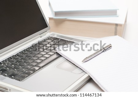 Office desk laptop with notepad and pen on white background
