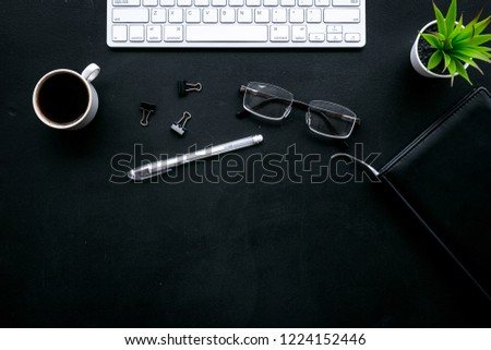 Office desk of chief, director or top manager. Computer keyboard, expensive black notebook, glasses, coffee on black background top view copy space #1224152446