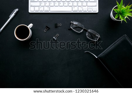 Office desk of chief, director or top manager. Computer keyboard, expensive black notebook, glasses, coffee on black background top view space for text #1230321646