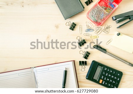 Office desk table with book planner, pen, calculator, wallet, pencil, ruler, stapler, paper clips, clamps, sharpener. Top view with copy space, flat lay. Business background. #627729080