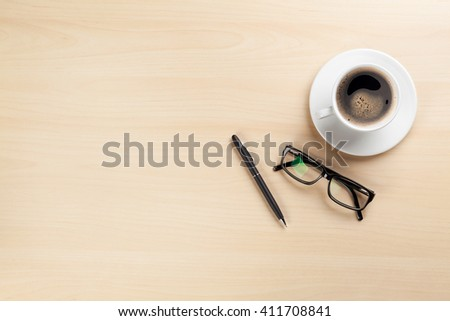 Office desk table with coffee cup, pen and glasses. Top view with copy space. Business office desk overhead view