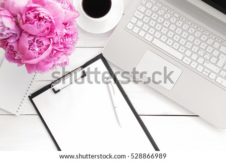 Office desk table with computer, supplies,  cup of coffee and peony flowers. White wooden background. Coffee break,  ideas, notes, goals or plan writing concept. Top view, flat lay.