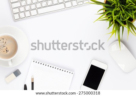 Office desk table with computer, supplies, flower and coffee cup. Top view with copy space