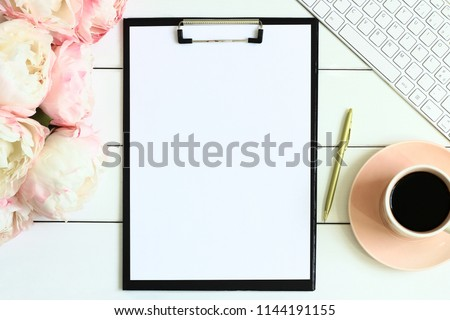 Office desk table with cup of coffee, pink peony flowers, golden pen, blank paper and clipboard. White wooden background. Coffee break, ideas, to do list, plan or note writing concept. Top view.