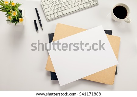 Office desk table with keyboard, notebook, pen, cup of coffee and flower. Top view with copy space (selective focus) #541171888