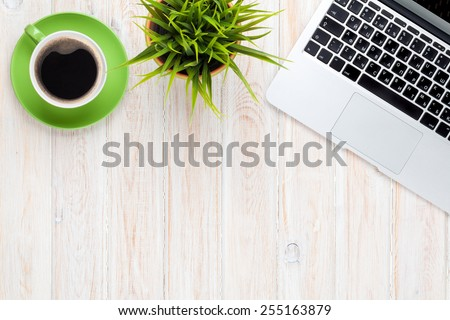 Office desk table with laptop computer, coffee cup and flower. Top view with copy space