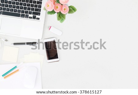 Office desk table with laptop, office supplies and flower pot. Top view with copy space.