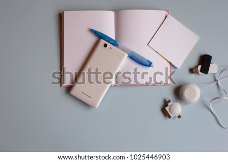Office desk table with notebook, smart phone, flash,pen. Top view with copy space. Working desk or school and study table with accessories. Accessories on light blue background. Concept of education. #1025446903