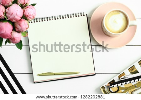 Office desk table with open notebook or sketchbook, pen, pink peonies and  cup of coffee. Coffee break,  ideas, notes, goals or plan writing concept. Top view, flat lay.