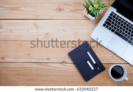 Office desk table with pen, keyboard on notebook, cup of coffee and flower. Top view with copy space (selective focus).