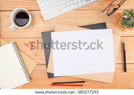 Office desk table with smartphone, pen on notebook, cup of coffee and flower. Top view with copy space (selective focus)