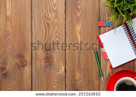 Office desk table with supplies, coffee cup and flower. Top view with copy space
