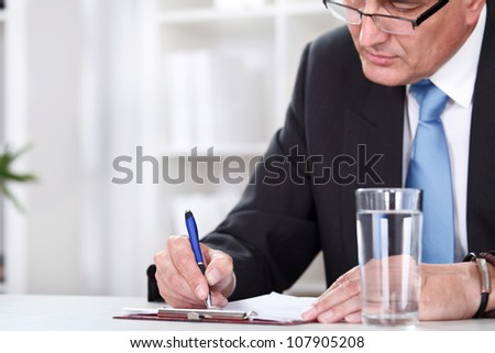 Office desk with business man signing a contract.