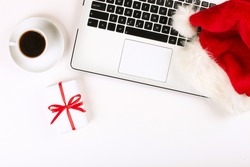 Office desk with coffee, laptop, christmas present and santa hat on white background flat lay with copy space. Business christmas holidays concept, holiday online shopping concept