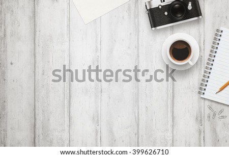 Photo of Office desk with free space for text. Camera, cup of coffee, paper, notepad, pencil on white wooden table. Top view.