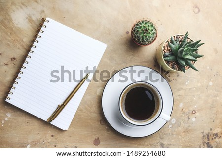 Office desk with hot coffee, plant, eyeglasses on beige stone background. Business desk minimal style concept with copy space. Top view. Flat lay