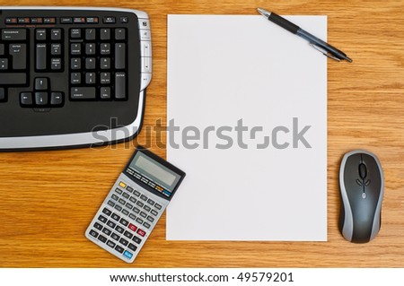 Office desk with keyboard, calculator, mouse, pen and a blank paper