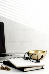 Office desk with laptop, notebooks, glasses