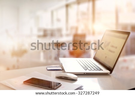 office desk with laptop smart phone and business office background.